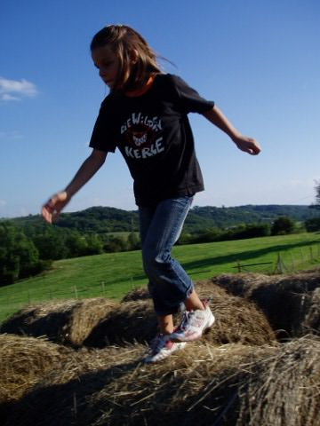 Jasmine jumping over the hay bales.