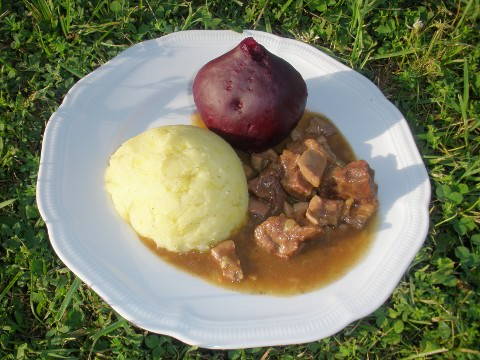 A photo of steak and kidney pie with mash and beet.