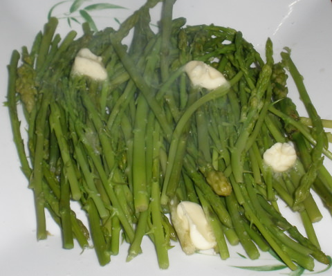 A bowl of cooked asparagus spears with butter