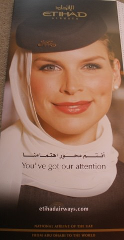 Etihad brochure with a photo of a stewardess.